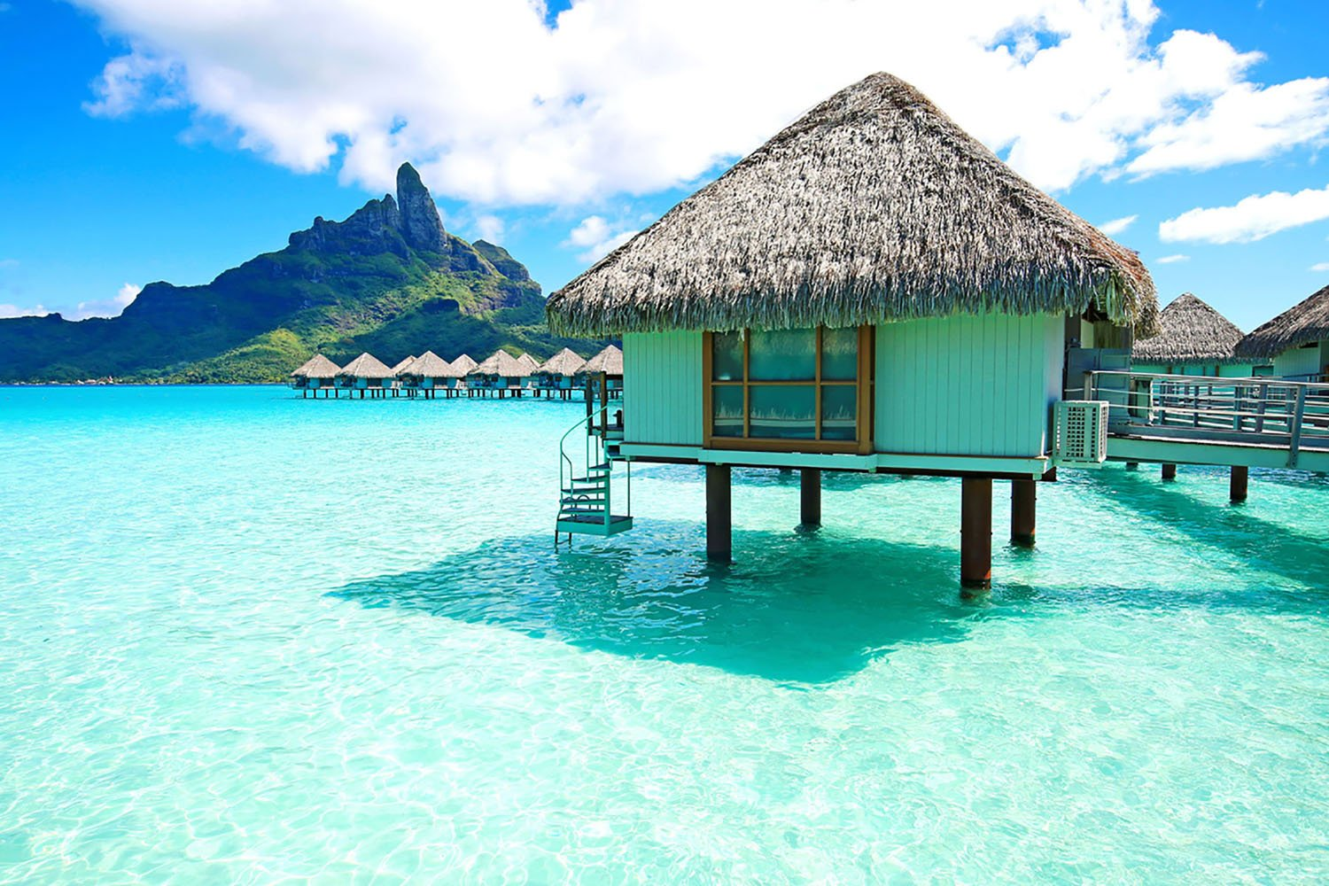 Grass-roofed huts on the beach in Bora Bora, French Polynesia.
