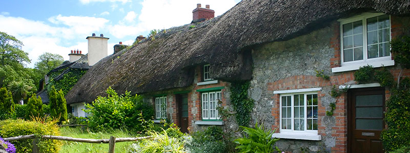 A stone cottage with a green lawn in Adare Village, Ireland.