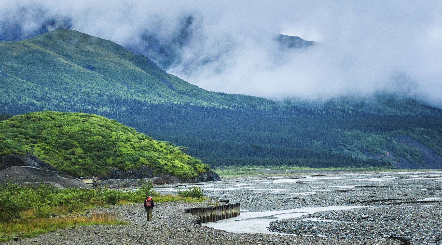 A photo of a lone backpacker on a trail in Alaska.