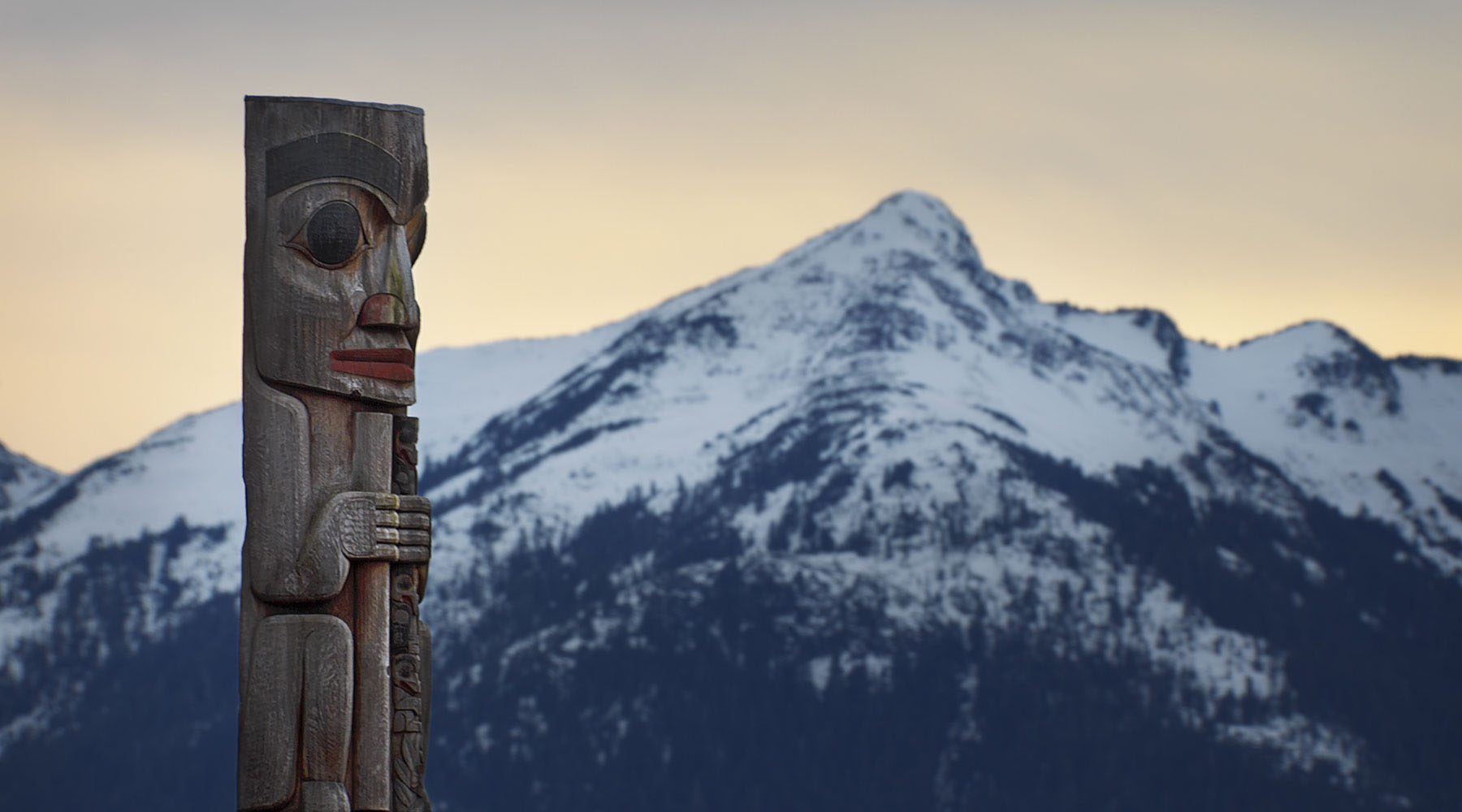 A simple photo of a totem photo and mountain range in Alaska.