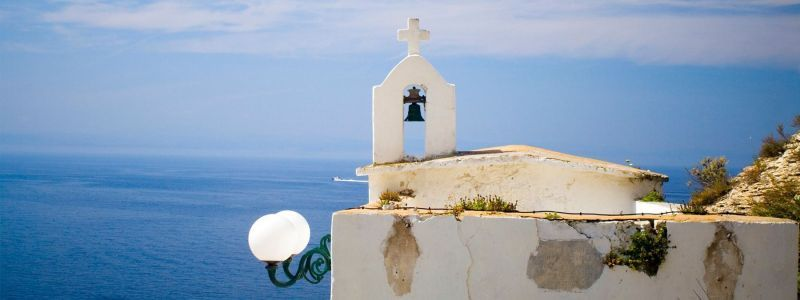 black bell with white concrete frame overlooking water in bonifacio corsica