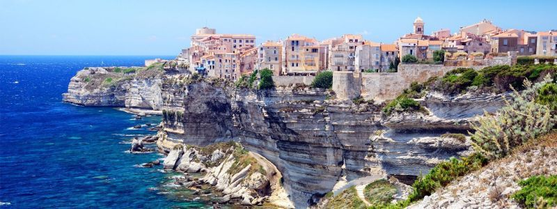 houses on cliffs overlooking blue water in bonifacio corsica