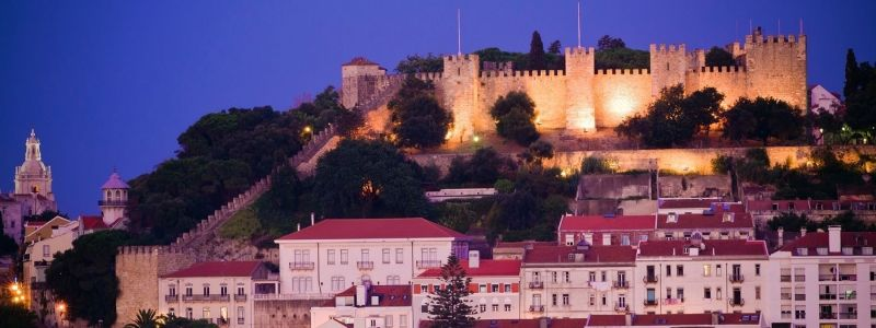 a castle atop houses at dusk in portugal lisbon