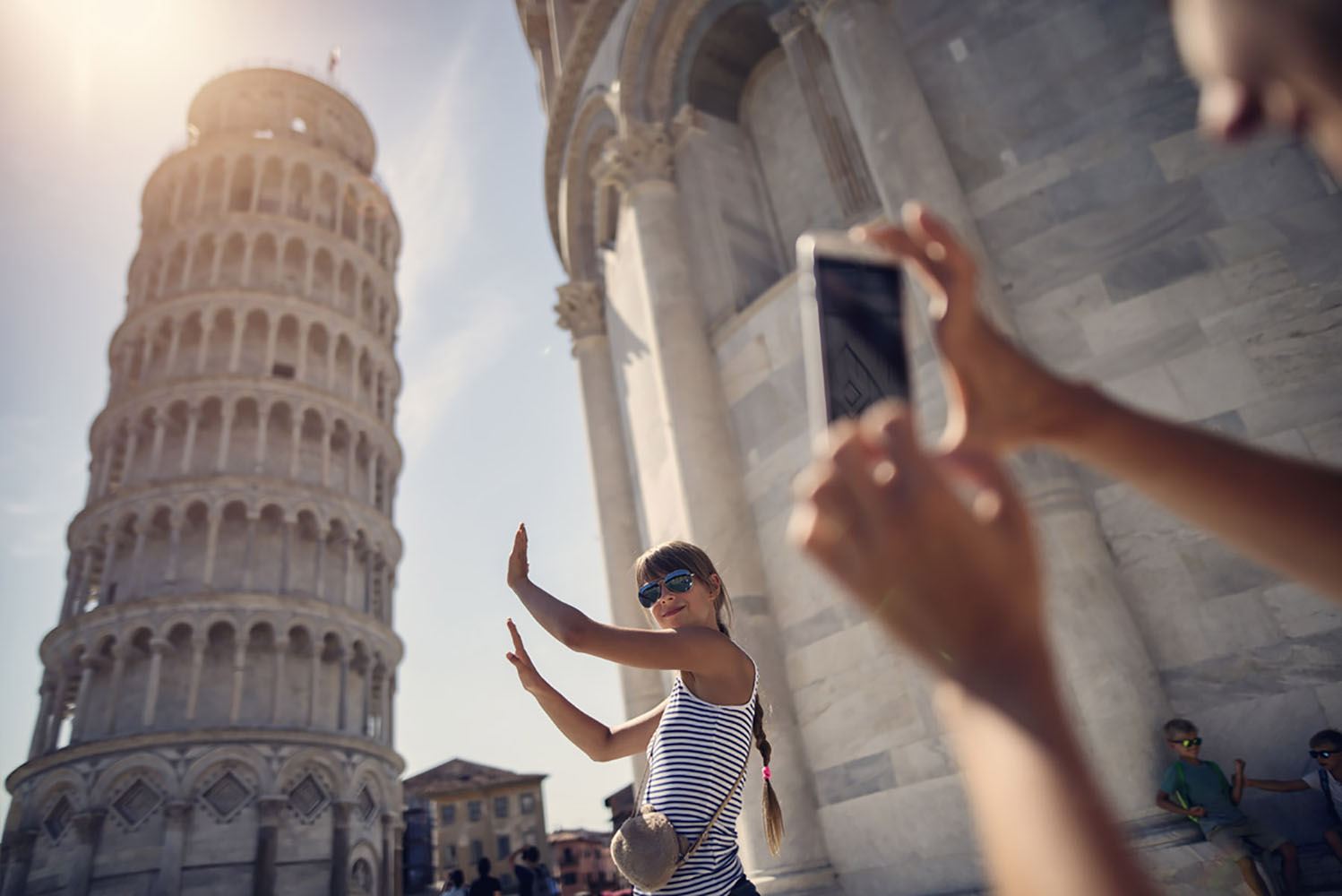 A lady recreates an iconic photo op near the Tower of Pisa