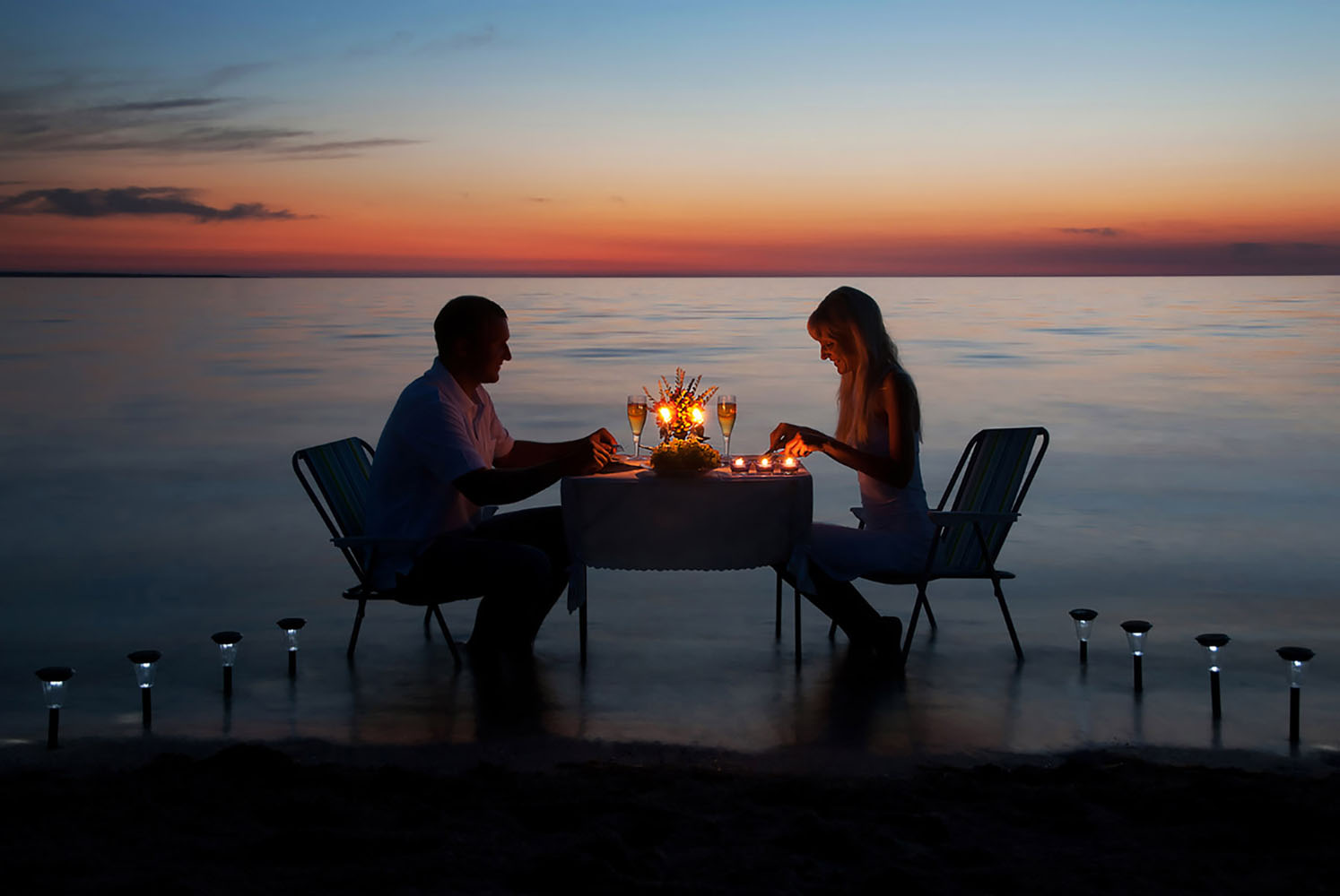 A couple enjoy a romantic candlelit dinner
