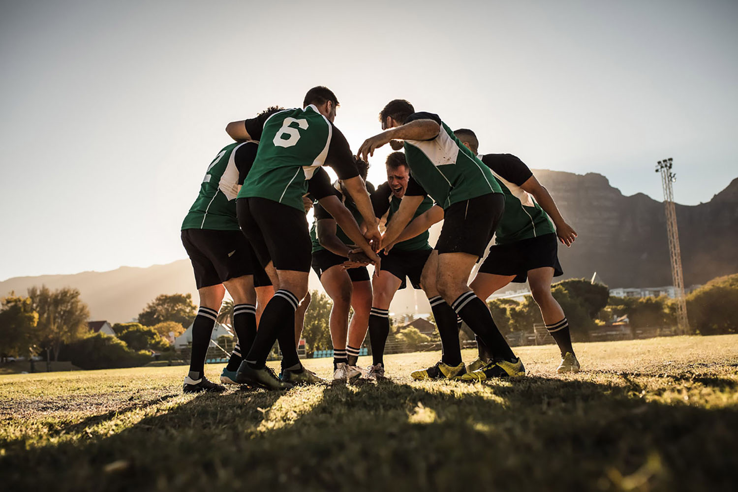 Rugby players gather in a scrum before the start of a match