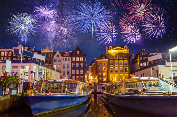 Traditional old buildings and boats with fireworks in Amsterdam