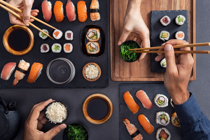 Top view of couple hands eating sushi food at Japanese restaurant