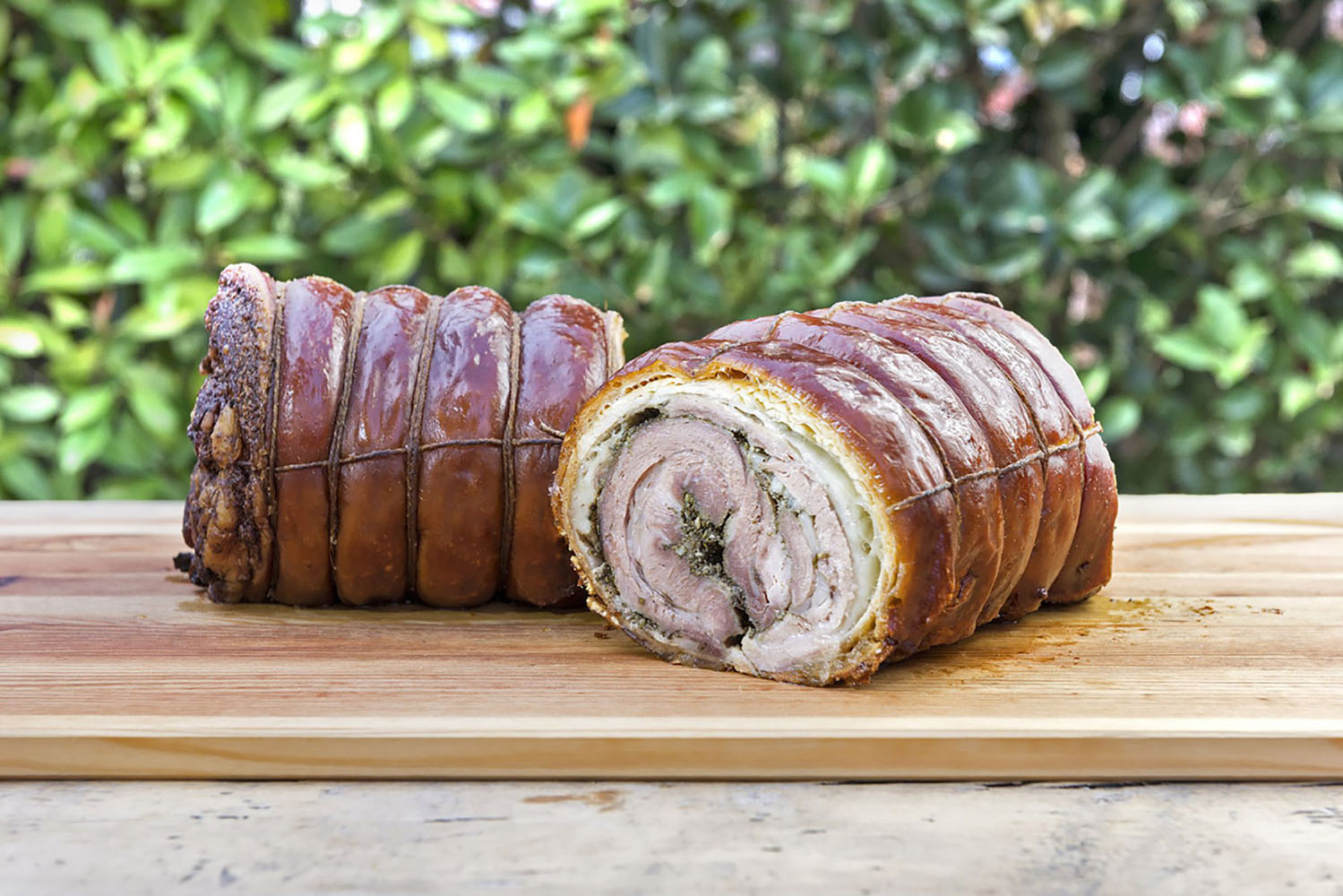 Porchetta cut in half on chopping board