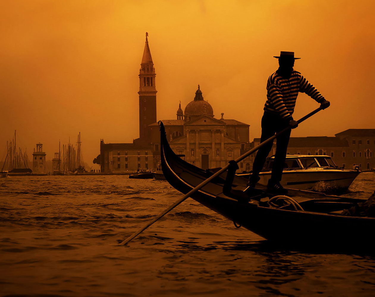 A gondolier guides his gondola through a Venice canal in the orange glow of sunset.