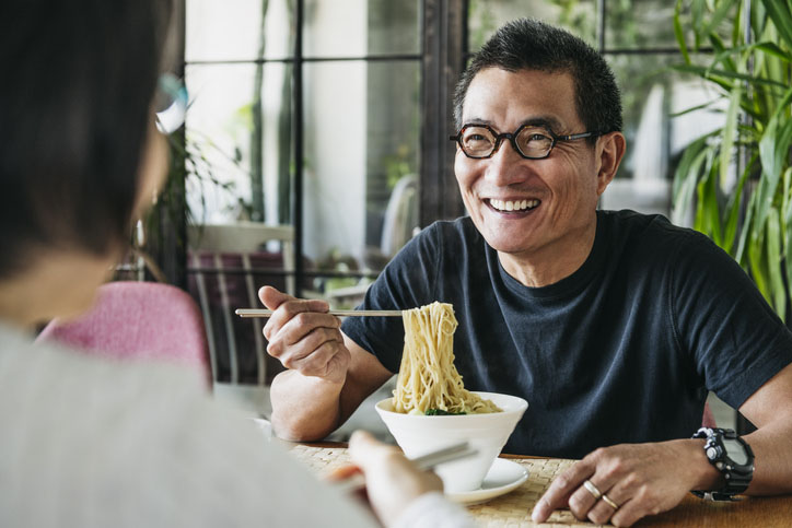Mature man eating bowl of noodles and laughing