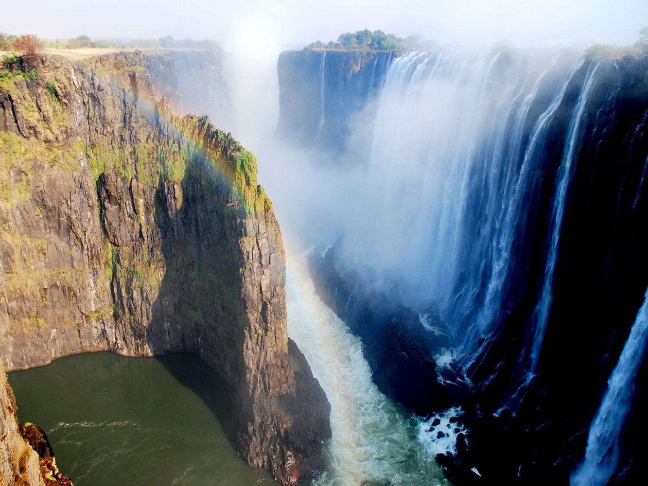 An aerial shot of Victoria Falls waterfalls, with a rainbow.