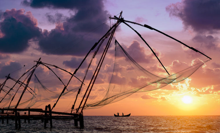 Sunset over Chinese Fishing nets and boat in Cochin