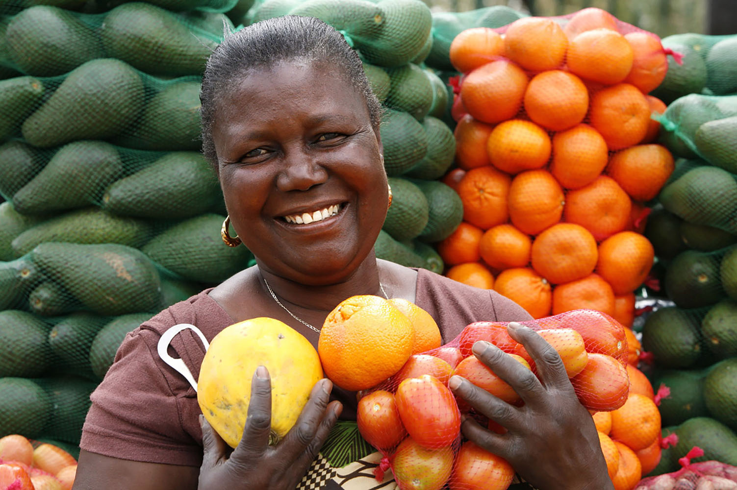 A fruit and vegetable seller poses in front of her produce.