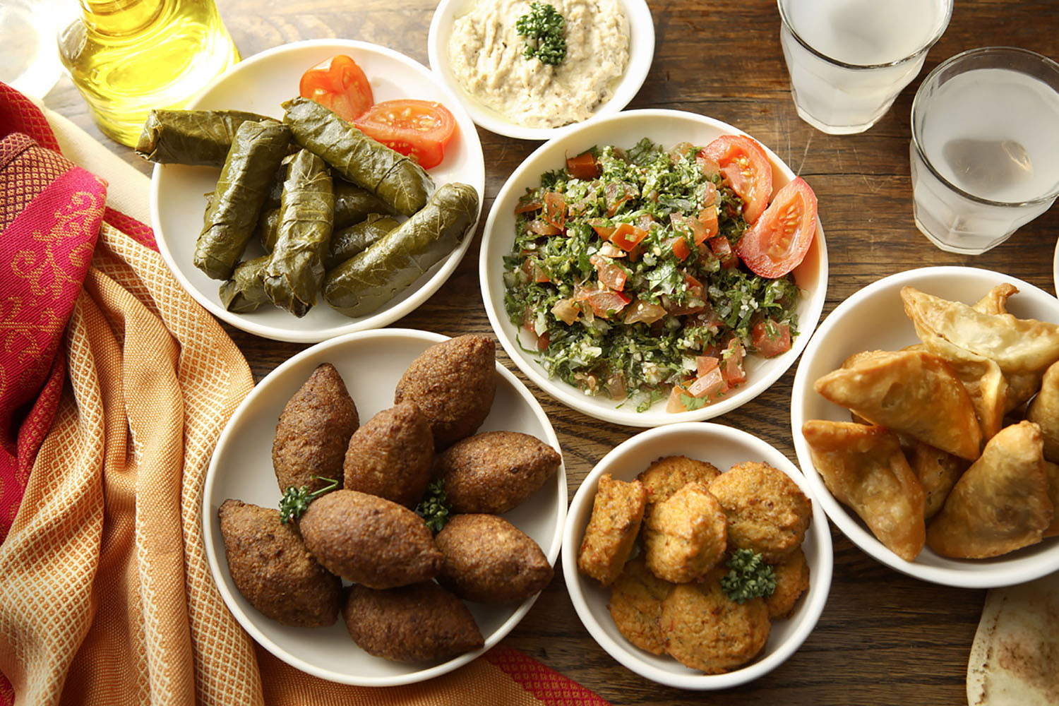 Mediterranean mezzes, including grape leaf rolls and falafel.