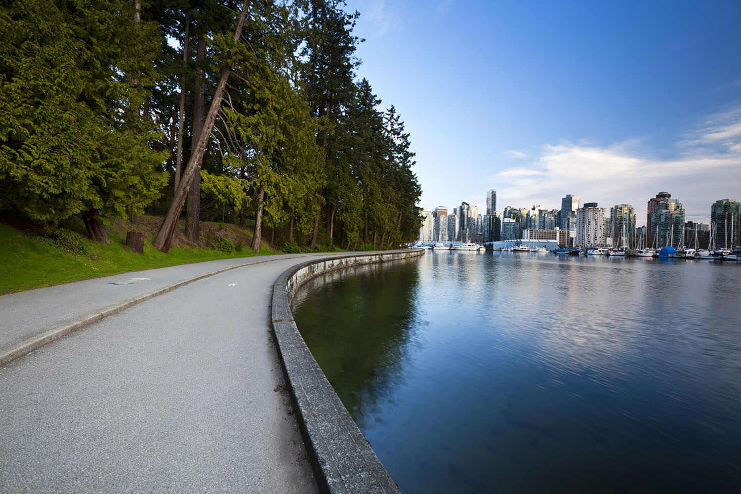 The Stanley Park Seawall in Vancouver with a view of the city skyline.