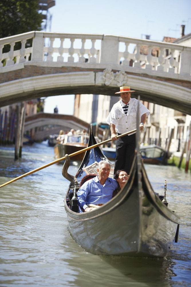 A couple travels by gondola on canal in Venice, Italy