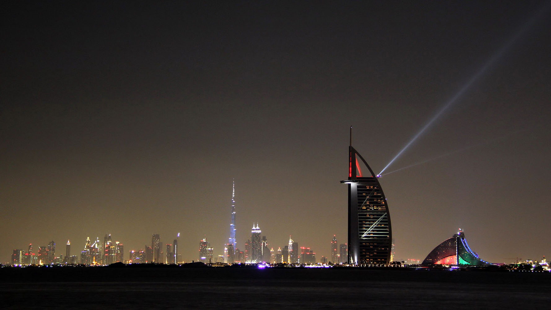 The Burj al Arab lit up with colorful lights on a Dubai evening