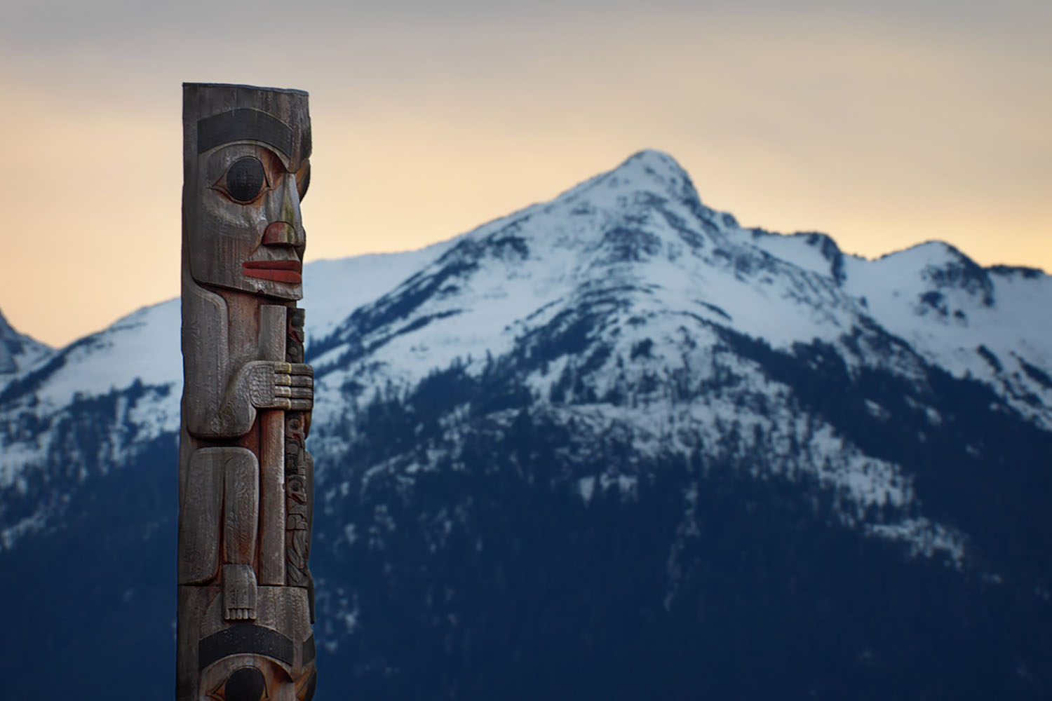A totem pole looking towards and mountain in Alaska.