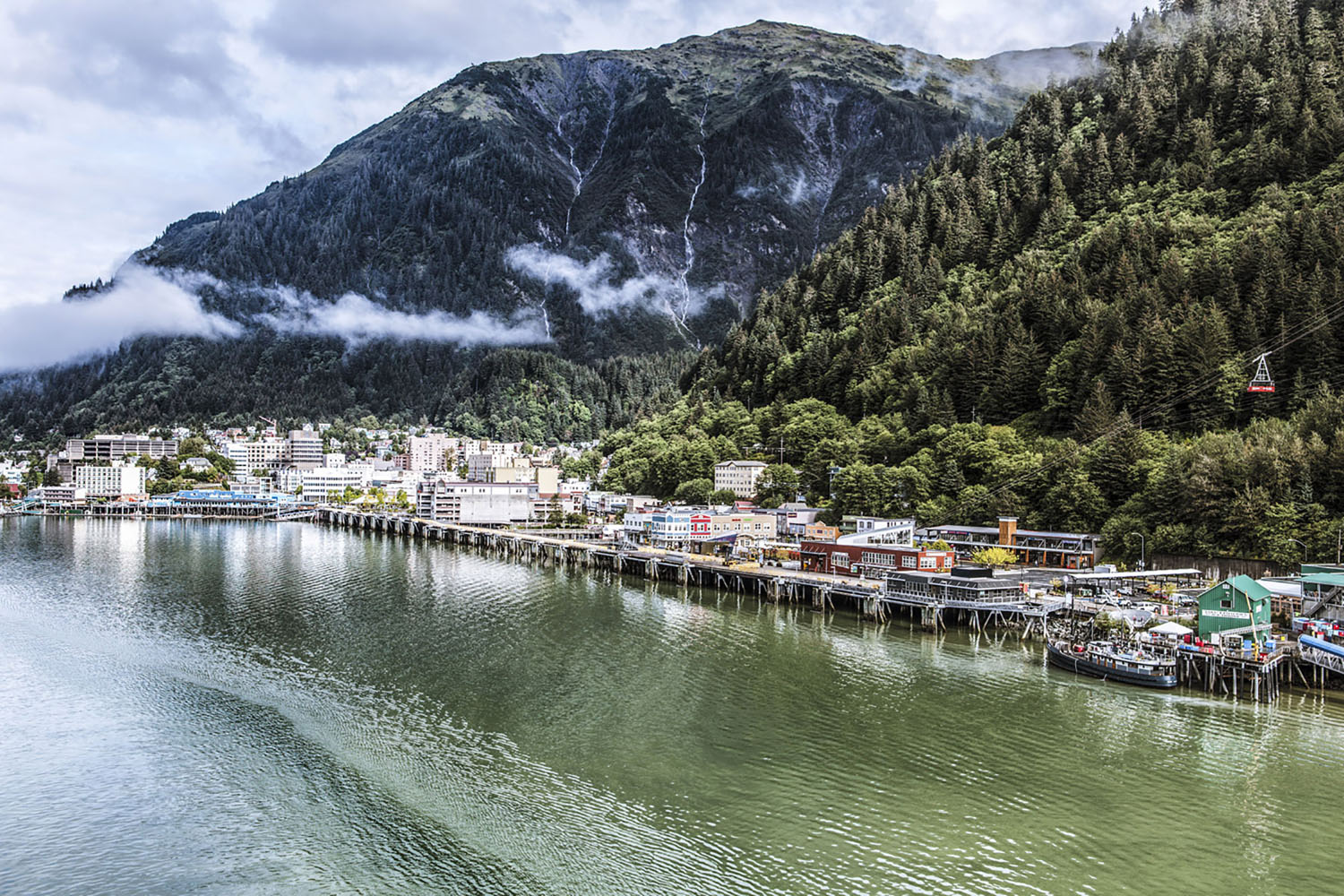 The waterfront of Juneau, Alaska is surrounded by lush green mountains.