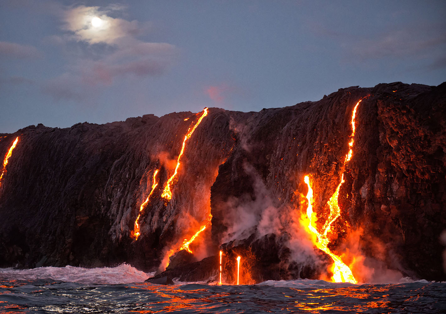 Lava flows into the water on an evening in Hawaii