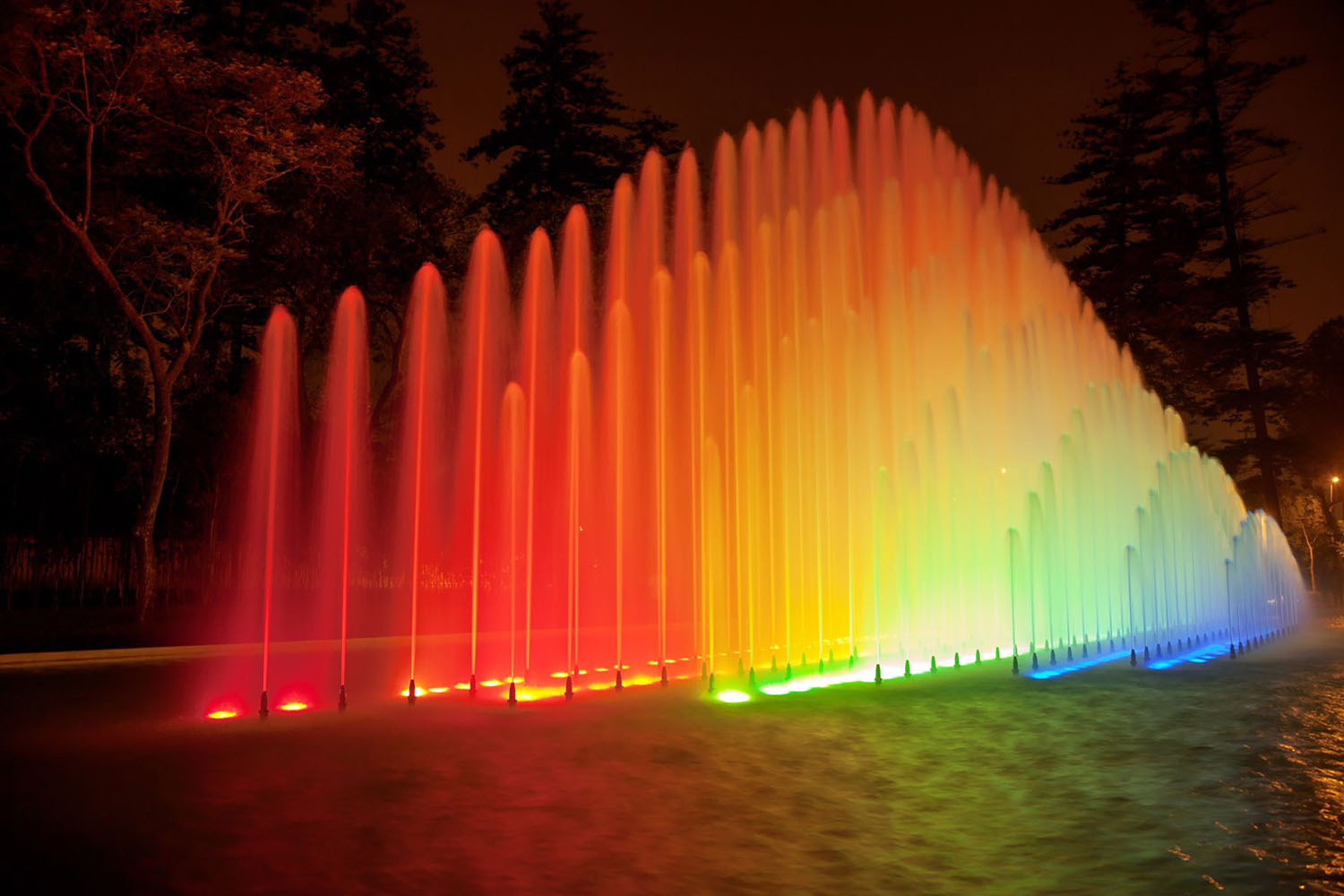 Colorful rainbow fountain at night in Park of the Reserve, Lima, Peru