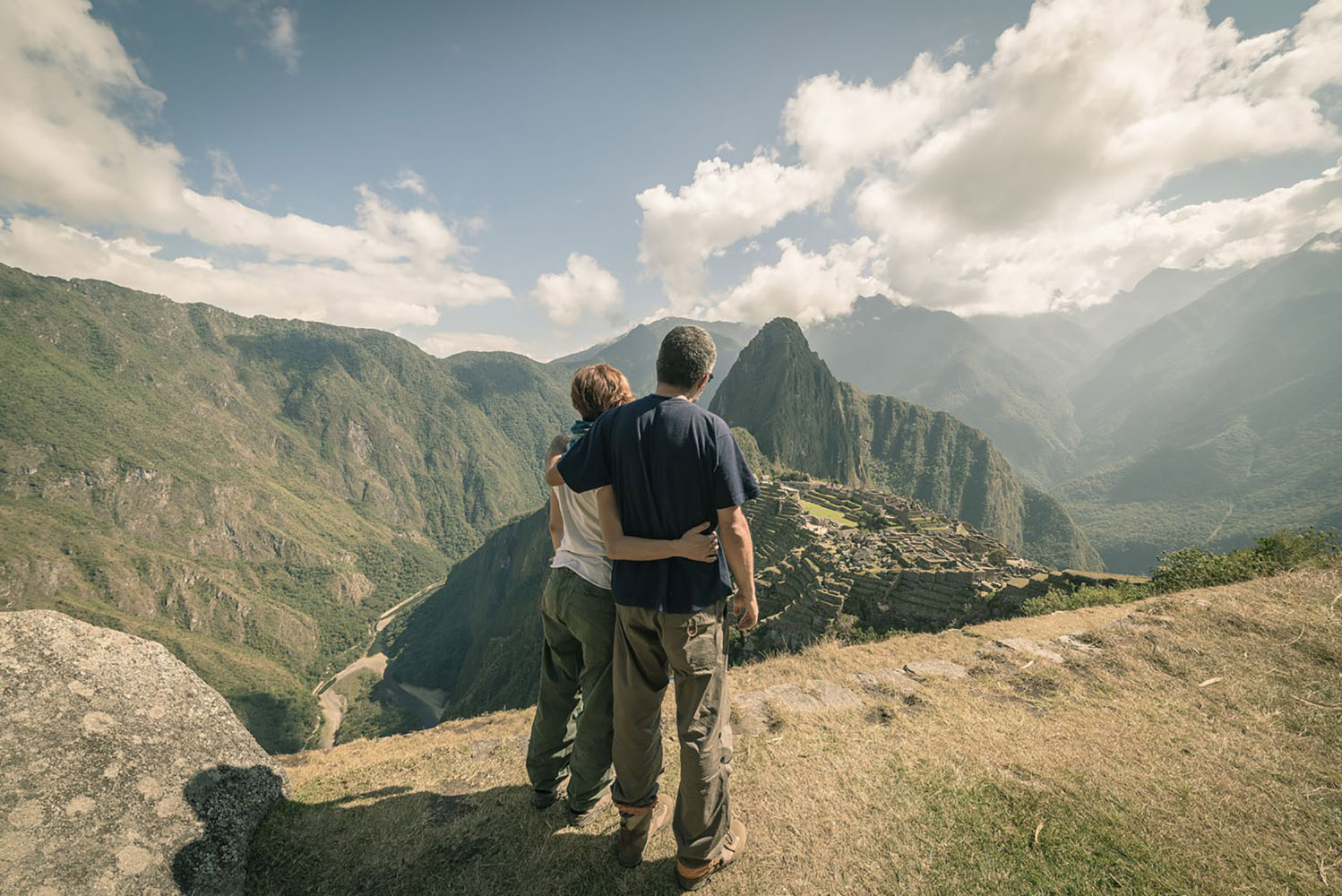Hugging couple looking at Machu Picchu