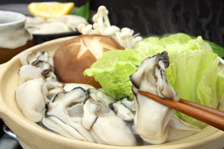 A Japanese dish containing oysters, vegetables, and Shiitake mushrooms boiled in a pot