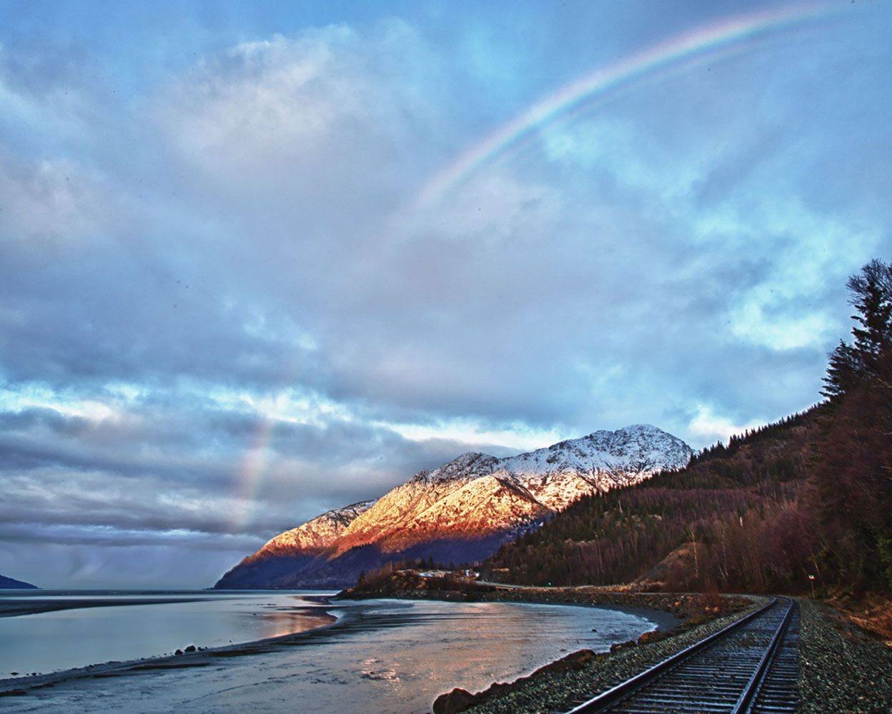 A rainbow stretches over a mountain range in Girdwood, Alaska.