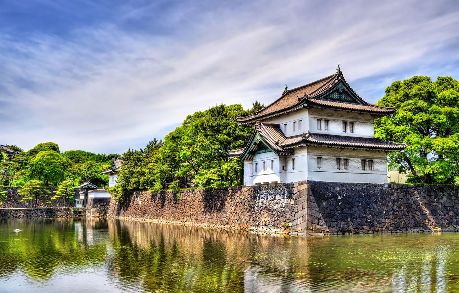A Japanese castle near the water on a sunny day