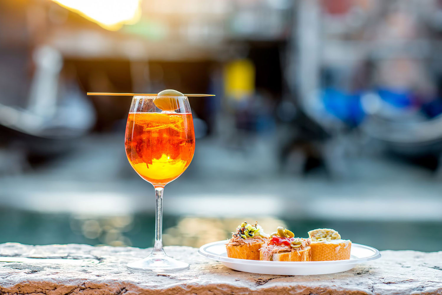 An Aperol Spritz cocktail is perched on a ledge in Venice, next to a plate of bruschetta.