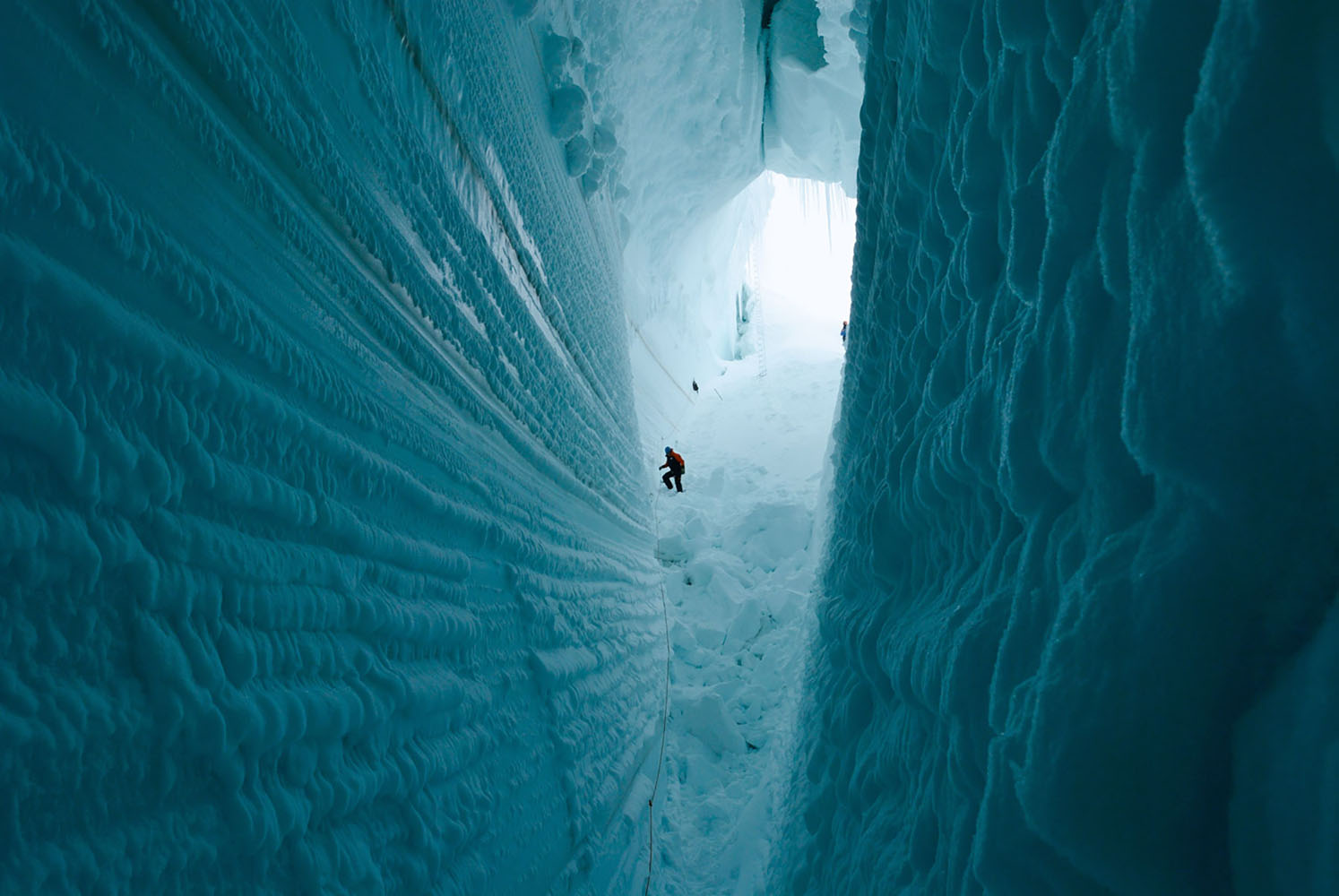 Researchers explore a deep crevice in Antarctica.