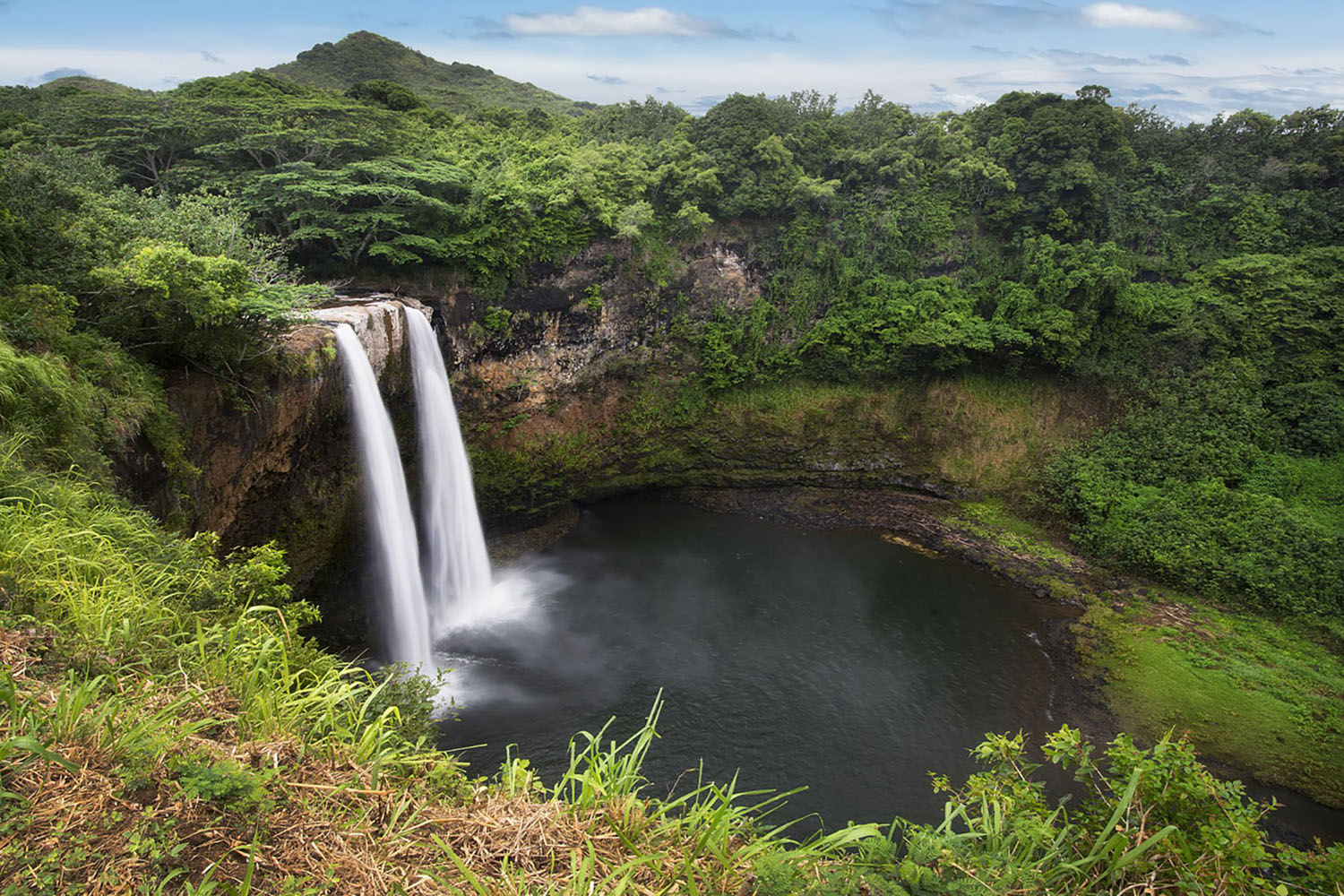 The Wailua Falls surrounded by lush green vegetation in Hawaii