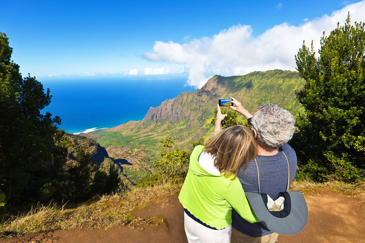 A man and woman take a photo on a hill overlooking the ocean in Hawaii