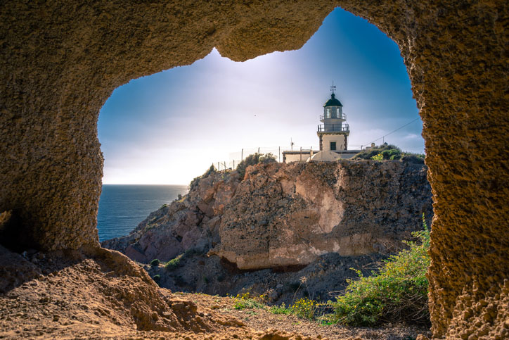Lighthouse at Akrotiri through a frame of a window of a cave,