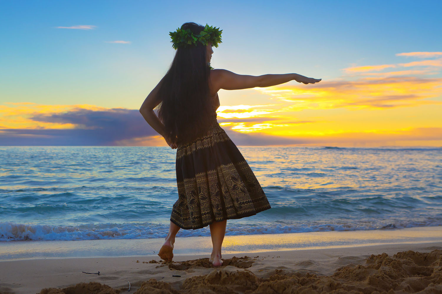 A Hawaiian woman dances in a luau as the sun sets beyond the beach