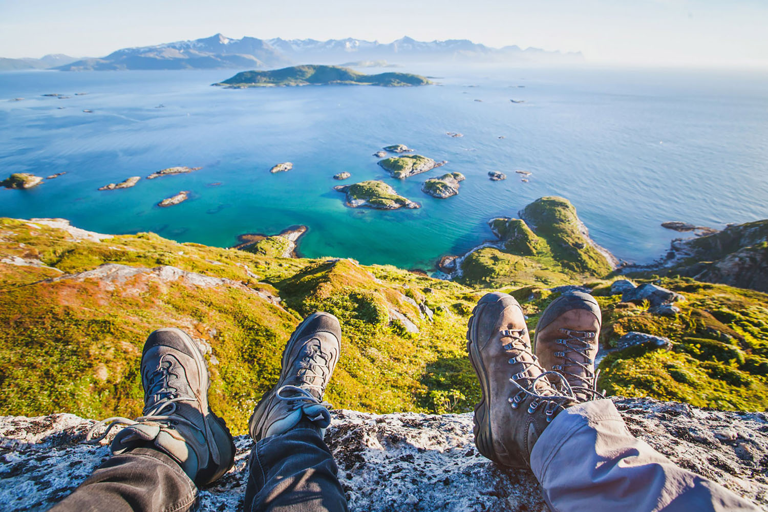 Two hikers overlook a lake in the Norwegian Fjords from a mountain top, with their hiking shoes in the foreground.
