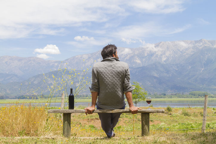 A man sits on a bench with a bottle of wine beside him and the mountains in the background