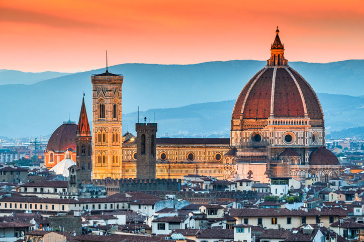 The Florence Cathedral illuminated in the city's skyline at sunset.