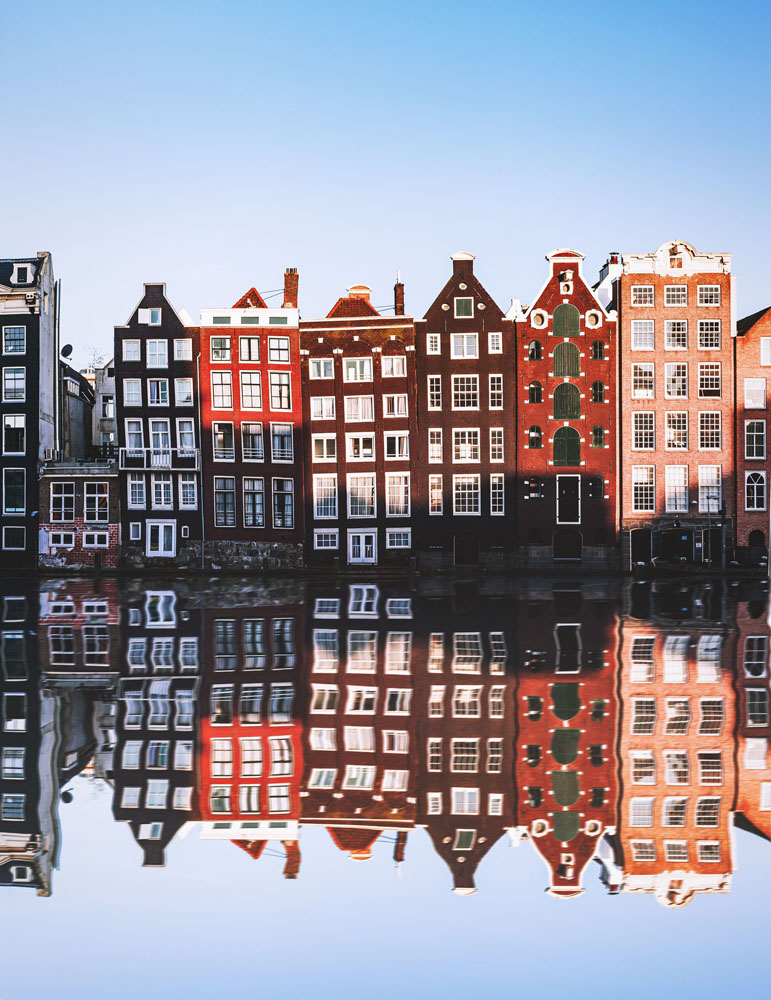 Crooked houses in Amsterdam reflect off the water