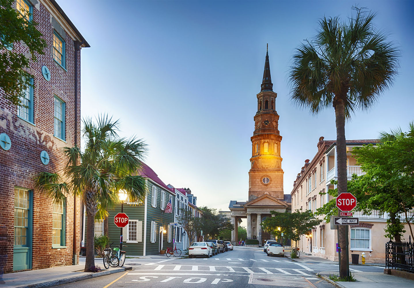 A Charleston ., South Carolina street at twilight with a church in the background