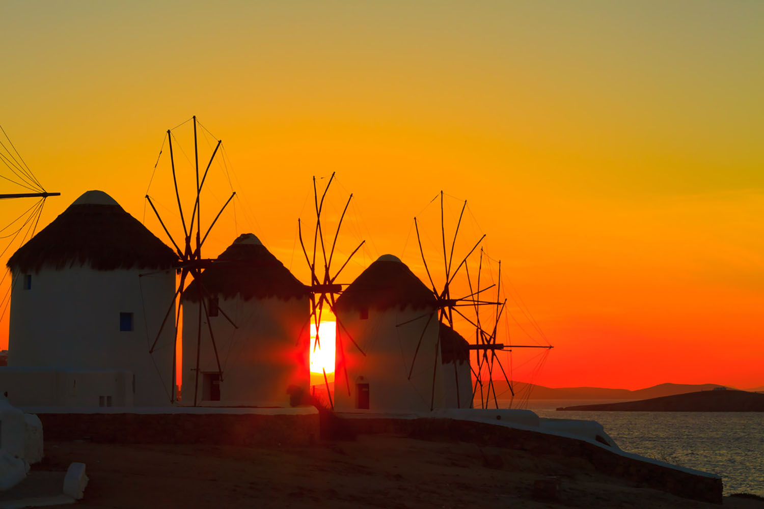 The windmills in Mykonos, Greece at sunset.
