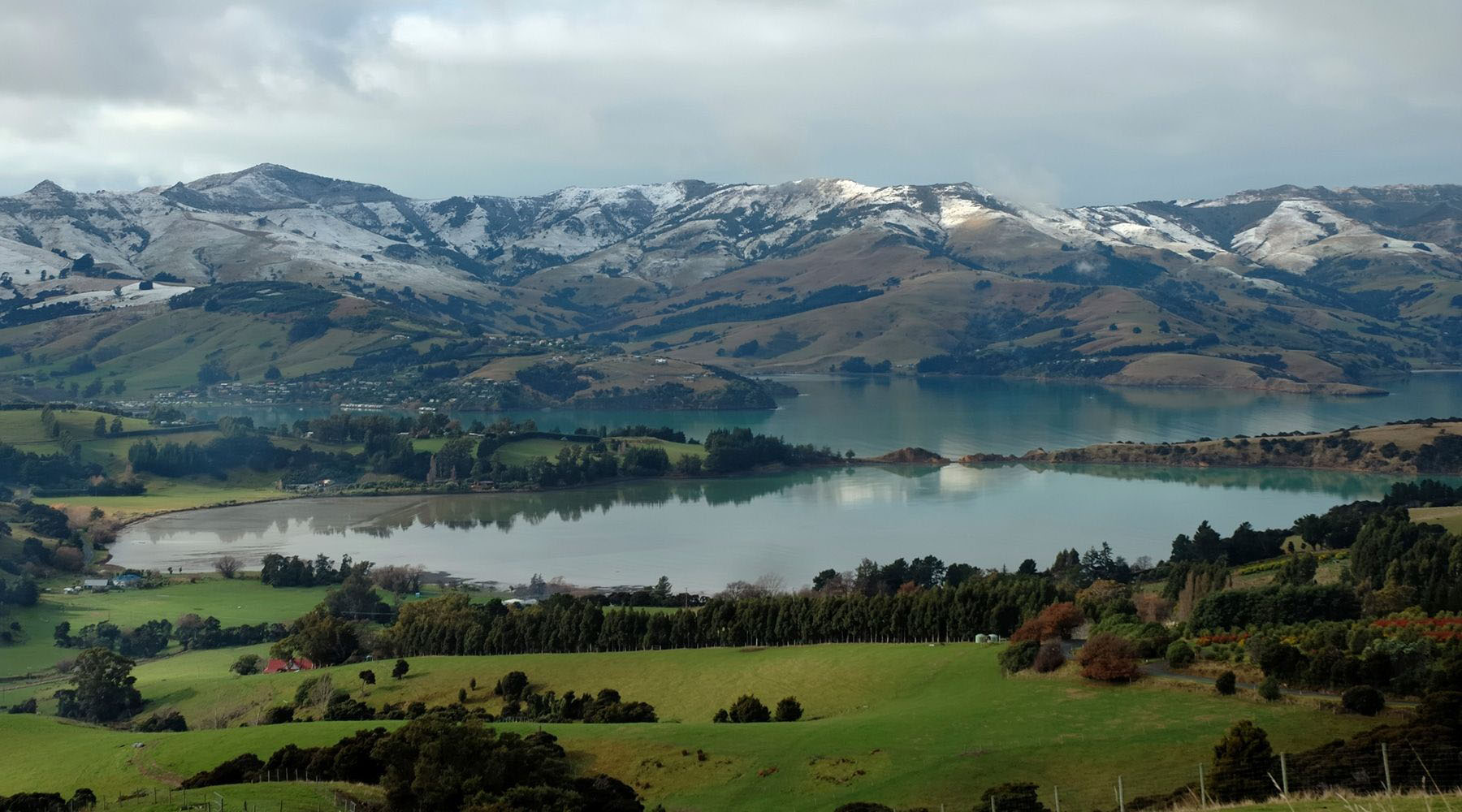 body of water surrounded by mountains in akaroa new zealand