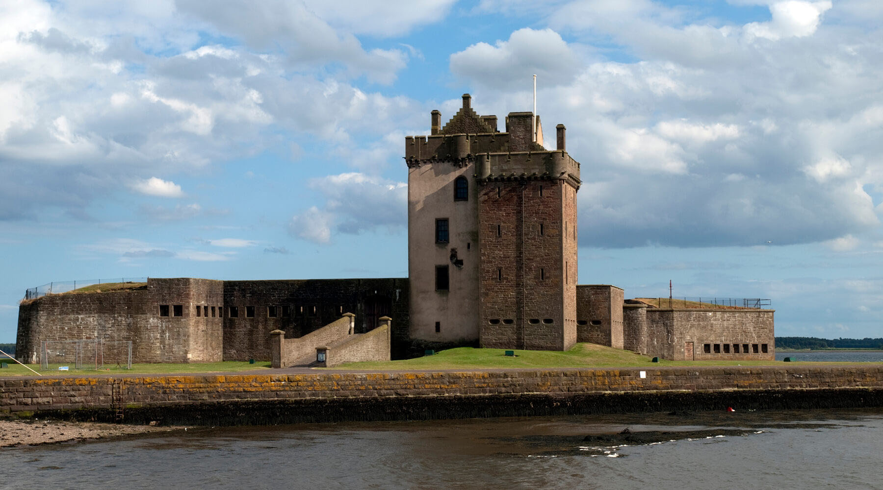 brown concrete castle near body of water under white cloudy sky in daytime in dundee scotland
