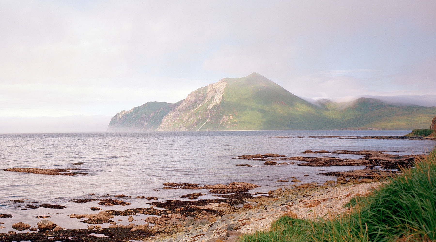 the misty green hills of Dutch Harbor Alaska as seen from the beach