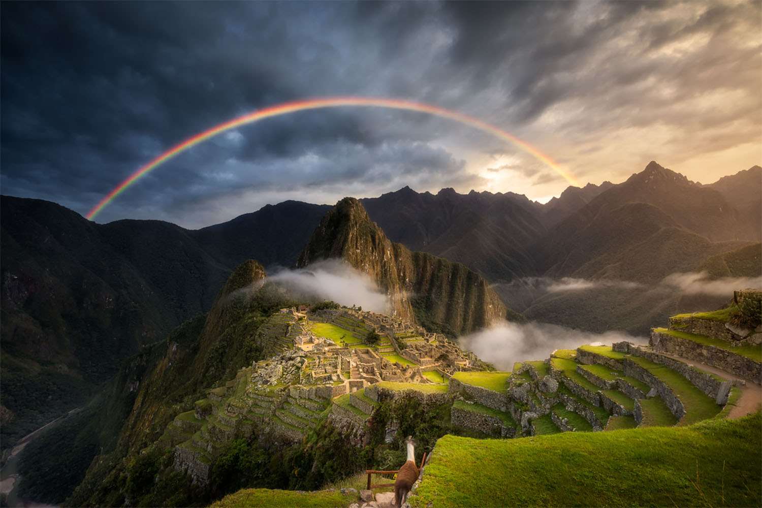 A rainbow arches across the sky over the archeological site of Machu Picchu