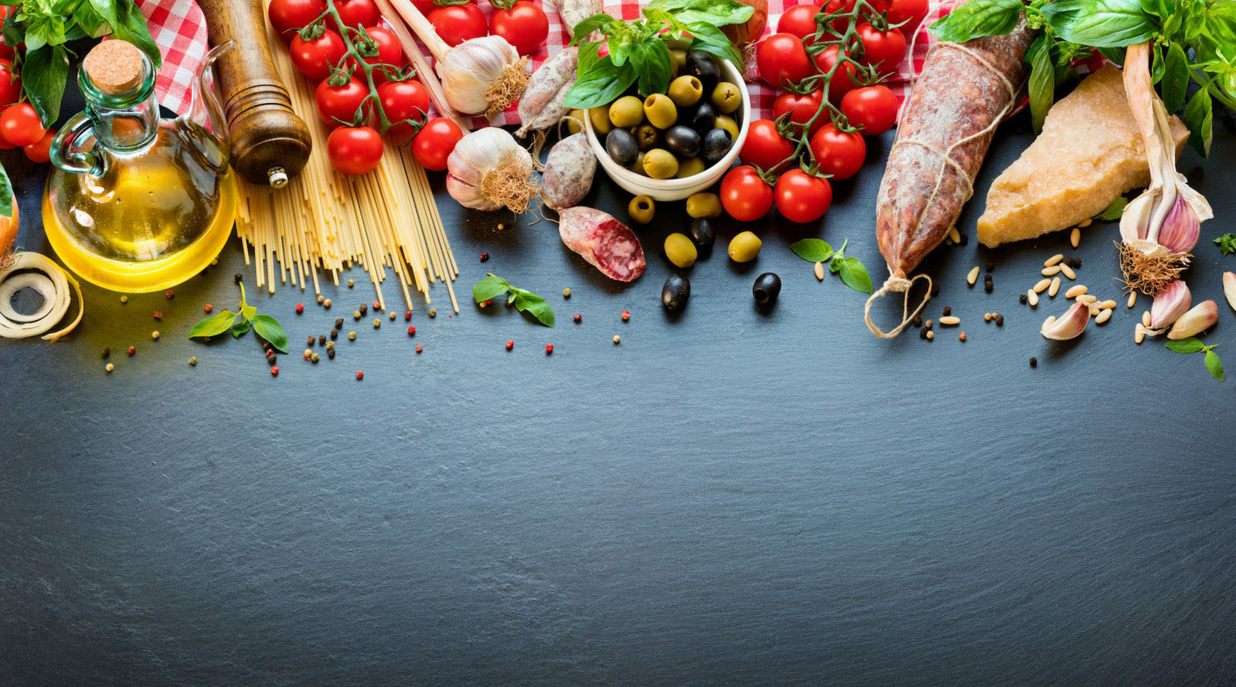A flat lay of Mediterranean food on a slate background.