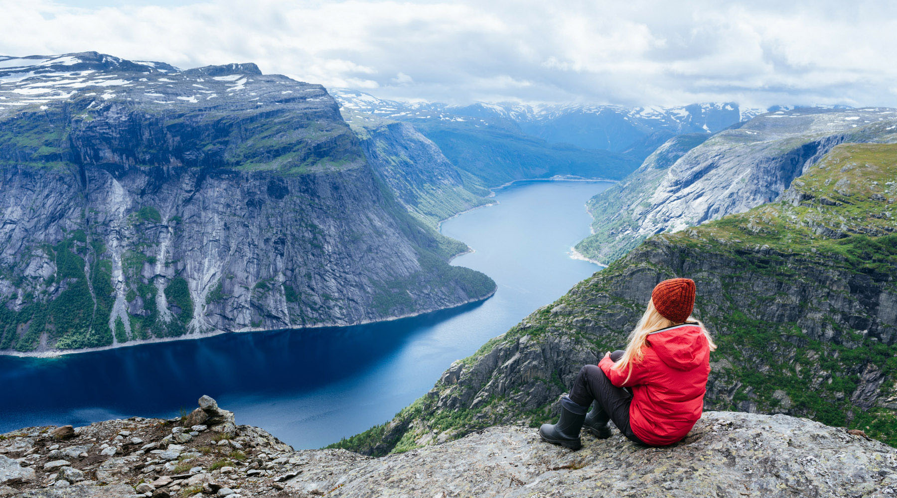 A woman in a red jacket sits on a mountaintop overlooking the fjords in Norway.