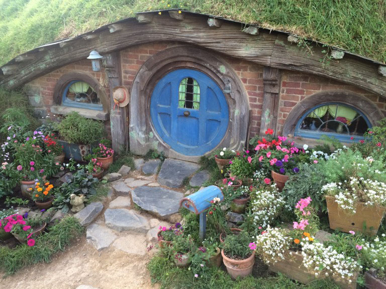 A hobbit house with a blue door from the hobbiton movie set
