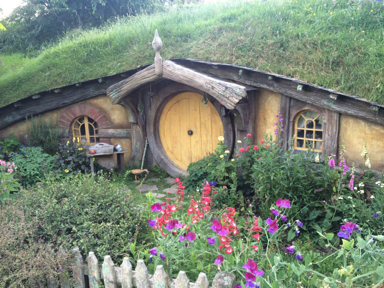 A hobbit house with a yellow door from the hobbiton movie set